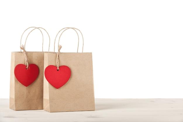 흰색 바탕에 하트 모양 태그가 있는 선물 골판지 가방