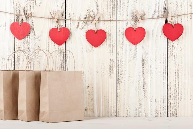 나무 배경에 하트 모양의 태그가 있는 선물 골판지 가방