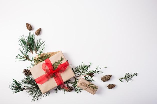 Подарок, новогоднее украшение, ветки кипариса, сосновые шишки на белом