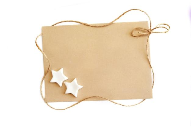 白い背景の上のフレームにクラフト紙とロープのシートとギフトクリスマステンプレートグリーティングカード。