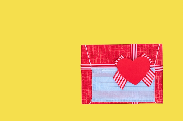 Gift concept during the coronavirus pandemic. red gift box with wearing a protective medical mask and red paper love heart on trendy illuminating yellow 2021 background, copy space