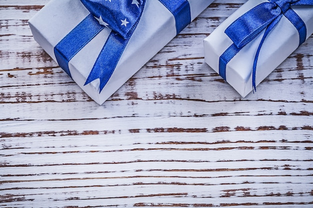Gift containers with blue present bows on vintage wooden board