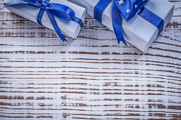 Gift containers with blue present ribbons on vintage wooden board