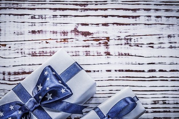 Gift containers with blue present tapes on vintage wooden board