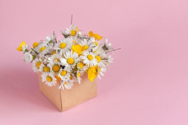Подарочная коробка с цветами ромашек на розовом