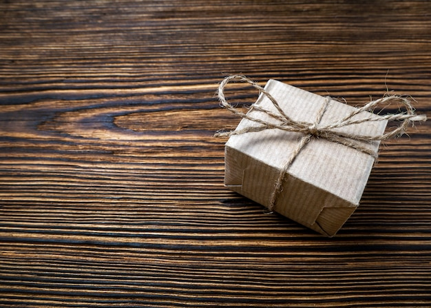 Gift craft paper box tied with jute rope on brown old wooden background