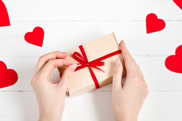 Gift in craft paper in female hands with hearts around on a white wood