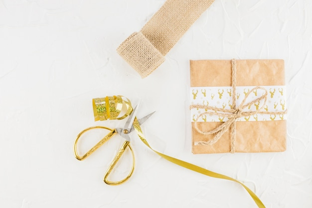 Gift in craft paper near scissors and ribbon
