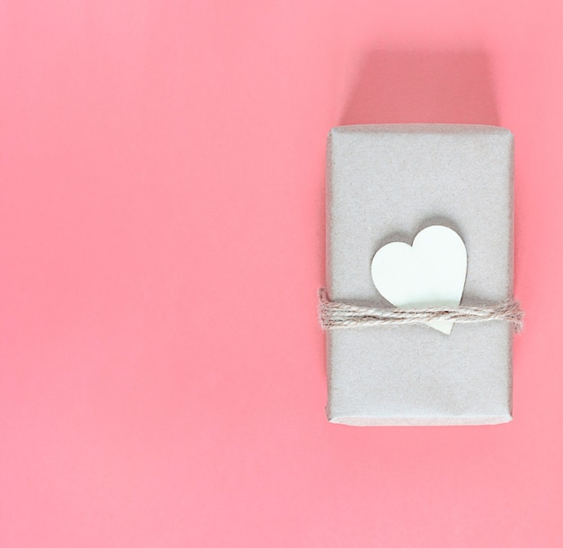 Gift in eco-friendly craft packaging and with wooden heart for the holiday on a pink background.