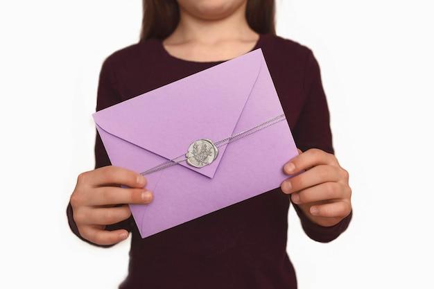 子供の手のギフト封筒女の子は手紙を持っています
