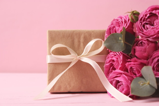 Gift and flowers on a colored background. holiday, give a gift, congratulations. valentine's day, mother's day, international women's day. high quality photo
