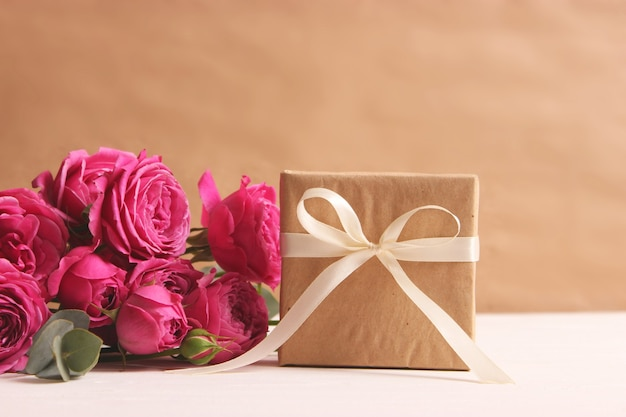 Gift and flowers on a colored background holiday give a gift congratulations
