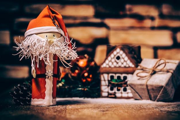 クリスマスプレゼント、ジンジャーブレッドハウス、おもちゃのサンタクロース。コピースペース付きの写真