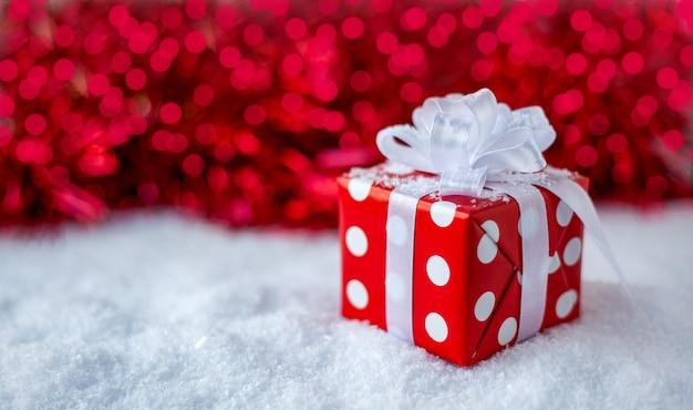 Подарок на новый год, рождество, день рождения белая коробка в горошек с большим бантом на красном фоне с боке