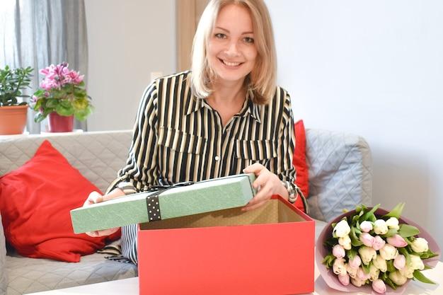 女性への贈り物。女の子はギフトボックスを開きます。驚きの喜び。花を持つ女性。誕生のお祝い。