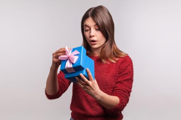 Подарок для вас. молодая женщина показывая настоящее и указывая на камеру.
