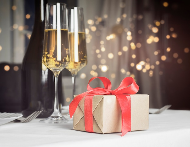 Gift and glasses of champagne with defocus lights wall