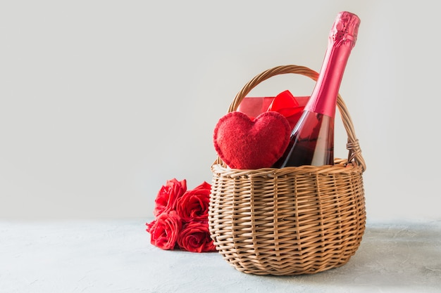 Gift hamper, bouquet of red roses,heart, bottle of champagne on white. valentines day card. romantic gift.