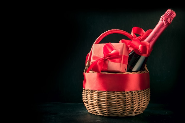 Gift hamper, red gift, bottle of champagne on black. isolated. romantic present.
