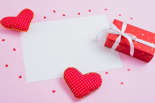 Gift and handmade hearts around paper