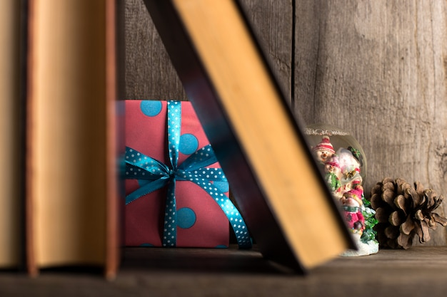 A gift hidden on a wooden shelf behind the books.