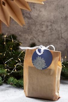 가문비 나무 화환과 화환의 배경에 대해 크래프트 종이로 만든 가방에 담긴 선물. 선택적 초점.