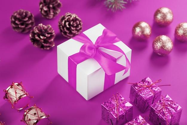 Подарок в белой коробке и елочные игрушки на розовой стене. розовая концепция из рождественских украшений