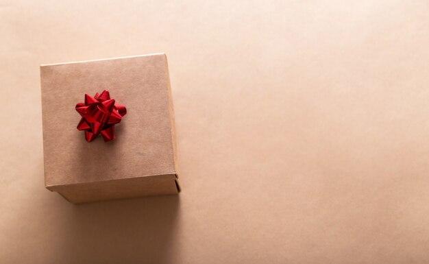 Подарок в крафтовой упаковке на крафтовой бумаге