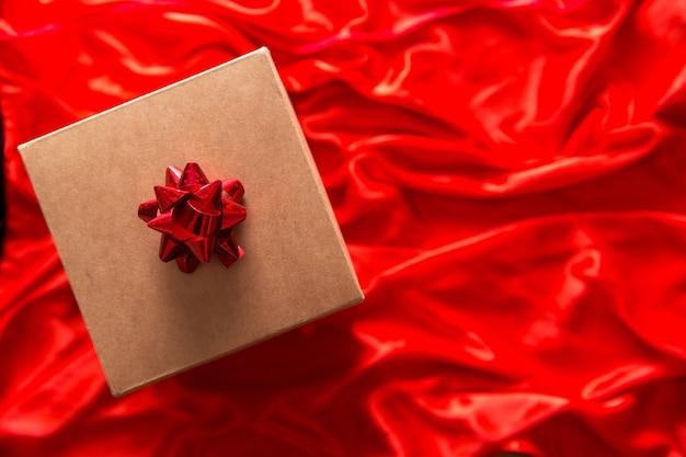 Подарок в крафтовой упаковке на красном шелке