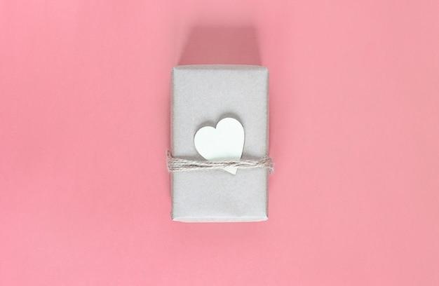 Подарок в экологически чистой крафтовой упаковке и с деревянным сердечком к празднику на розовом фоне.