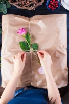 灰色の包装紙とピンクのバラ、女性の手の中の贈り物