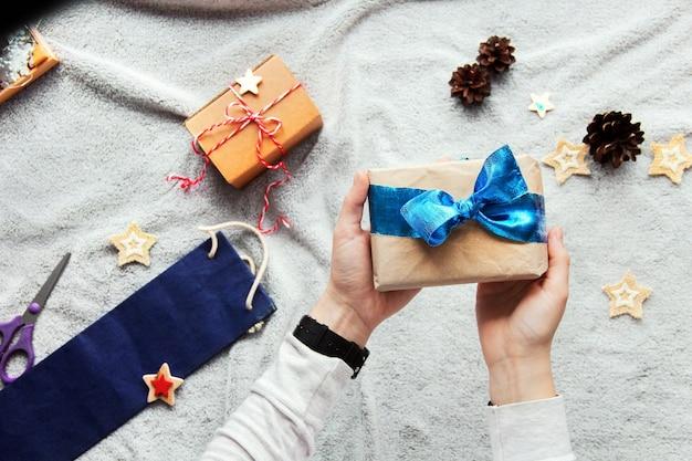 Подарок в руки. процесс упаковки подарков. синий бант. подарки в крафтовой бумаге. праздничная атмосфера. новогодний декор. минималистичная подарочная упаковка