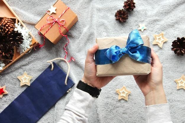 손에 선물. 선물 포장 과정. 블루 나비. 공예 종이에 선물. 축제 분위기.