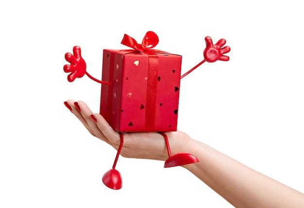 Подарок в красной коробке. на женской руке сюрприз в изящной коробке с ручками и ножками.