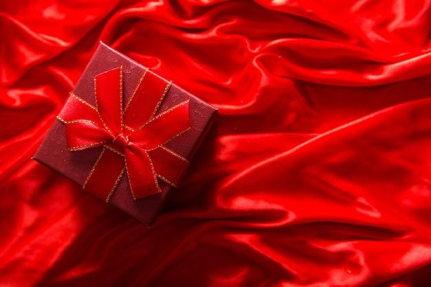 Подарок в красной упаковке на красном шелковом материале