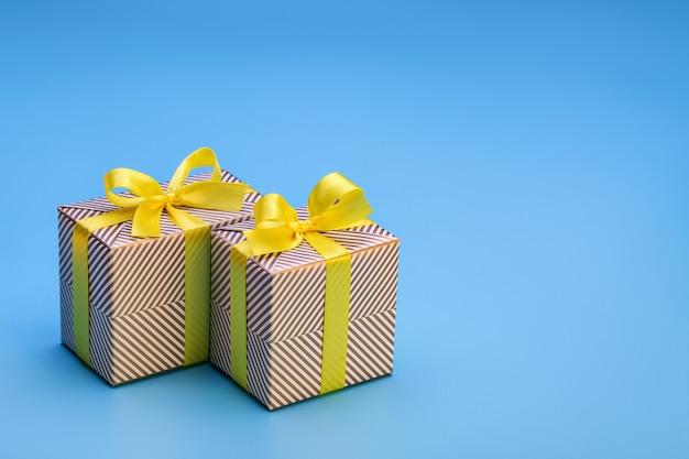 휴일 종이에 싸서 활과 노란색 리본으로 묶인 두 개의 상자에 선물. 나무 배경에 모든 휴일 및 이벤트에 대한 놀라움.