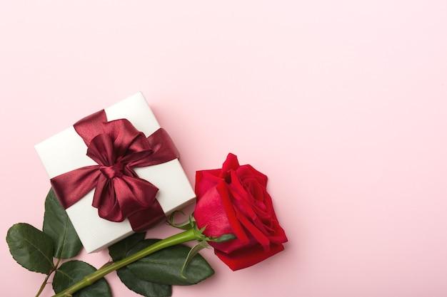 Подарок в белой, квадратной коробке, бордовая атласная лента, одна красная роза с листьями, розовый бумажный фон, вид сверху