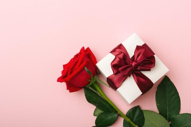 Подарок в белом, квадратная коробка, бордовая атласная лента, одна красная роза с листьями, справа, розовый бумажный фон, вид сверху
