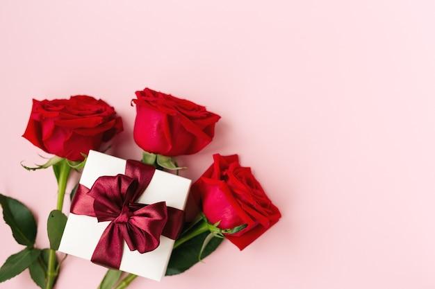 Подарок в белом, квадратная коробка, бордовая атласная лента, три красные розы с листьями, розовый бумажный фон, вид сверху, левая сторона