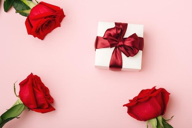 Подарок в белой, квадратной коробке, бордовая атласная лента, три красные розы с листьями, розовый бумажный фон, вид сверху