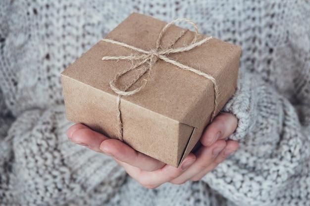 여자의 손에 선물, 클로즈업입니다. 흑백, 미니멀한 선물 컨셉입니다. 스웨터를 입은 소녀가 끈으로 묶인 크라프트지로 만든 선물 상자를 들고 있습니다. 놀라운 배경입니다.