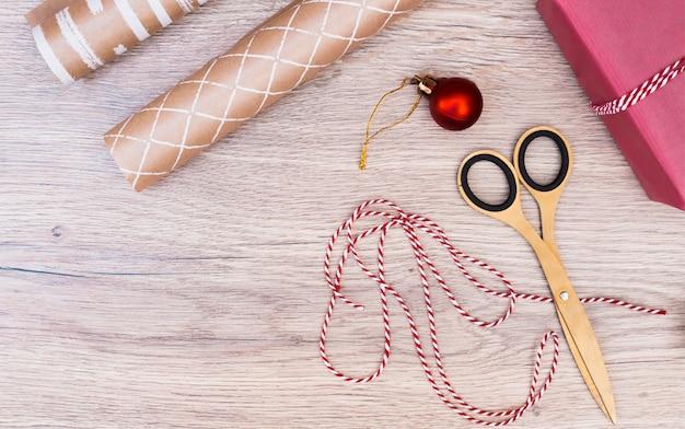 Подарок в обертке возле новогоднего шара, нитки и ножницы