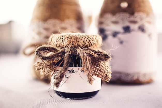 Gift jar for guests in rustic style with a white sign.
