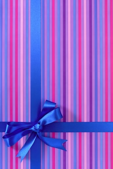 Подарок из фиолетовой полосатой бумаги с синей атласной лентой.