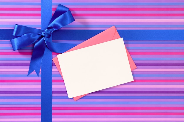 Подарок из полосатой бумаги с синим атласным ленточным розовым конвертом и пустой карточкой сообщения
