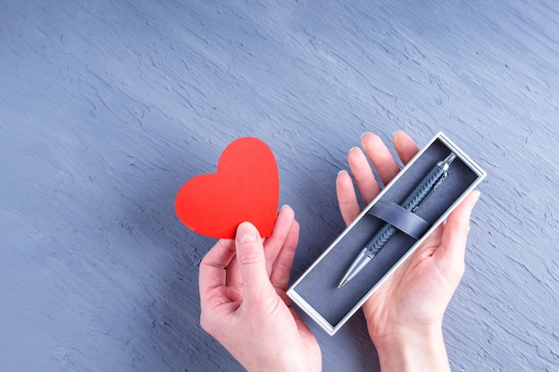 Gift for a man. female hands hold a box with a pen and a paper heart shape