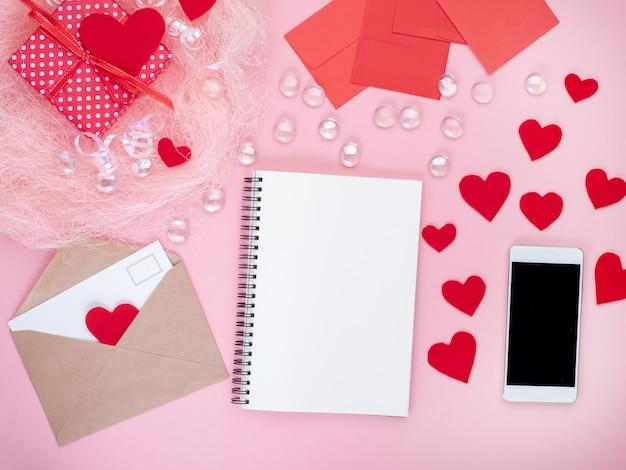 ギフト、メモ帳、封筒、カード、赤いハート、ピンクの背景、フラットレイアウト、コピースペース