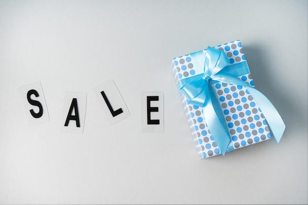 Подарок на сером фоне в синей упаковке. концепция черной пятницы на день подарков.