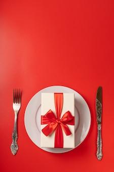 Подарок на сервировочной тарелке на красной стене