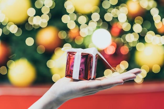 Подарок под рукой с рождественскими огнями боке